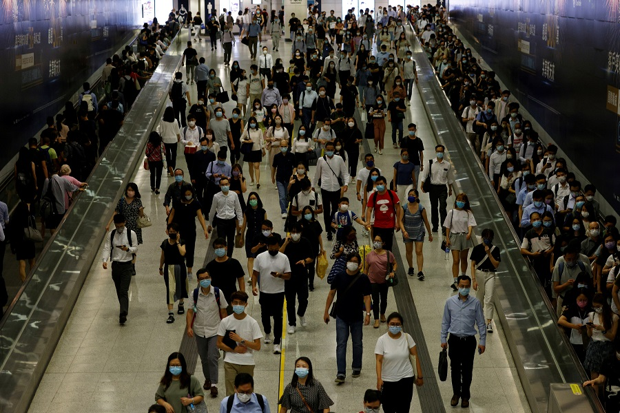 Passengers wearing protective masks walk through the Central Mass Transit Railway (MTR) station in Hong Kong,  17 August 2021. (Tyrone Siu/Reuters)