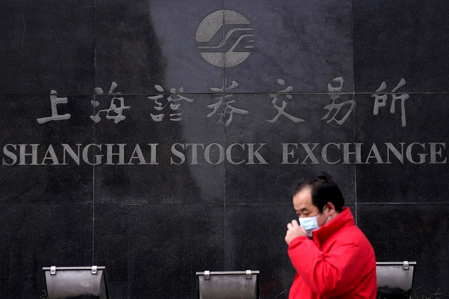 A men wearing a mask walks at the Shanghai Stock Exchange building at the Pudong financial district in Shanghai, China, 3 February 2020. (Aly Song/File Photo/Reuters)