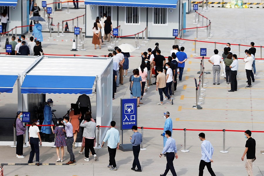 Staff members of Shanghai Pudong International Airport line up at a nucleic acid testing site to test for the Covid-19 coronavirus in Shanghai, China, 20 August 2021. (CNS photo via Reuters)
