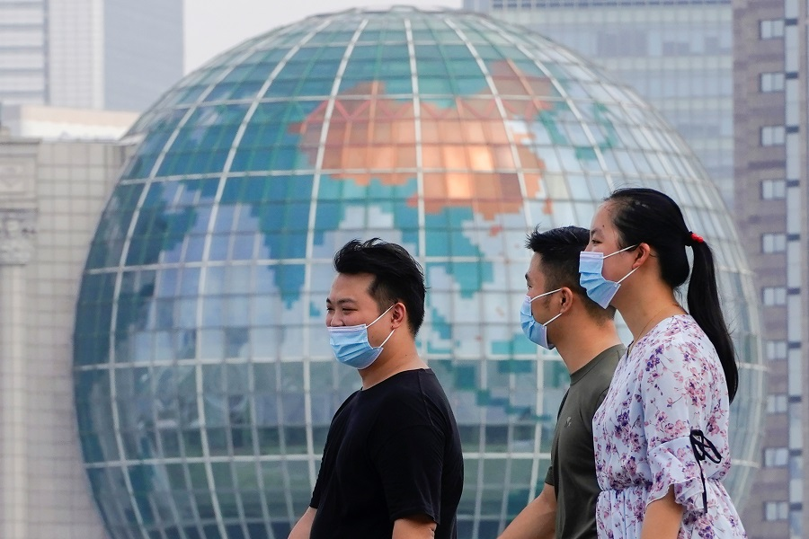 People wearing protective face masks walk along The Bund in front of the Lujiazui financial district of Pudong, in Shanghai, China, 25 August 2021. (Aly Song/Reuters)
