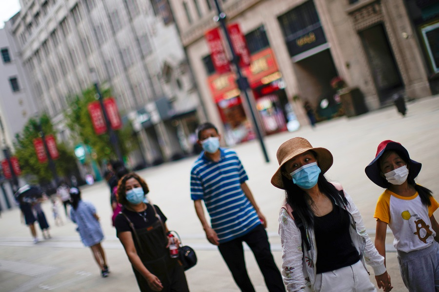 People wearing protective face masks walk on a street in Shanghai, China, 25 August 2021. (Aly Song/Reuters)