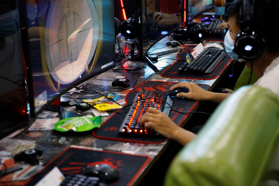 A man plays an online game on a computer at an internet cafe in Beijing, China, 31 August 2021. (Florence Lo/Reuters)