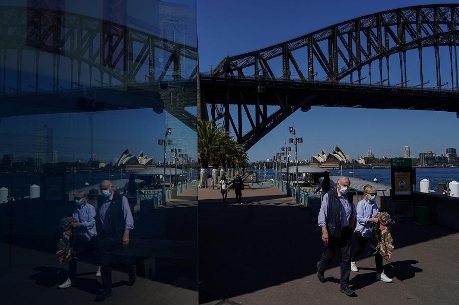 People in protective face masks walk past the Sydney Harbour Bridge in Sydney, Australia, 3 September 2021. (Loren Elliott/Reuters)