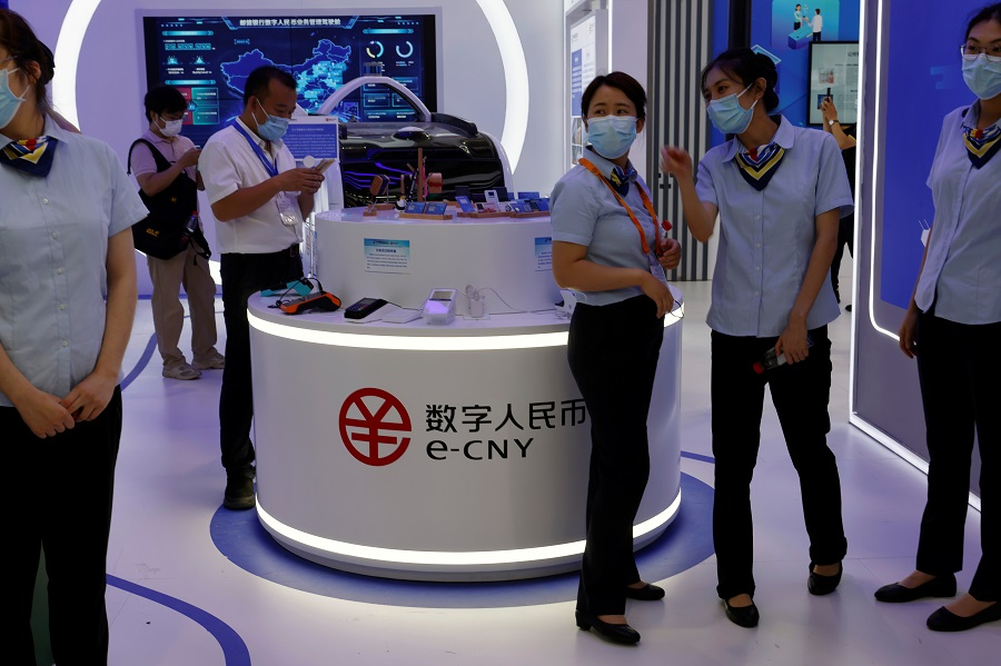 Staff members stand near a counter promoting China's digital yuan, or e-CNY, at the 2021 China International Fair for Trade in Services (CIFTIS) in Beijing, China, 3 September 2021. (Florence Lo/Reuters)