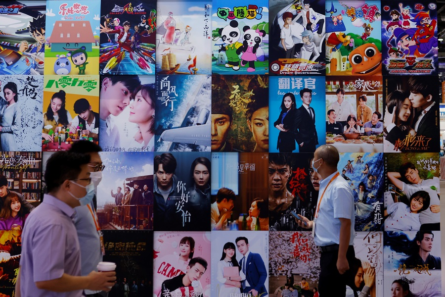 People walk past a display of posters for Chinese movie and television productions at the 2021 China International Fair for Trade in Services (CIFTIS) in Beijing, China, 4 September 2021. (Florence Lo/Reuters)