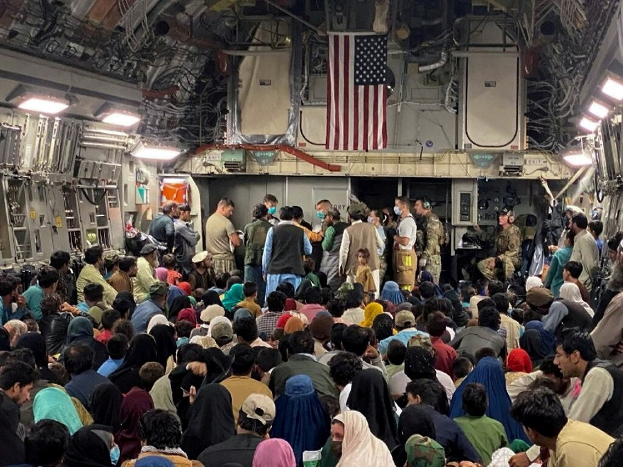 A newborn baby is looked after prior to taking off with other Afghan evacuees on a C-17 Globemaster III at a Middle East staging area, 23 August 2021. (US Air Force//Handout via Reuters)