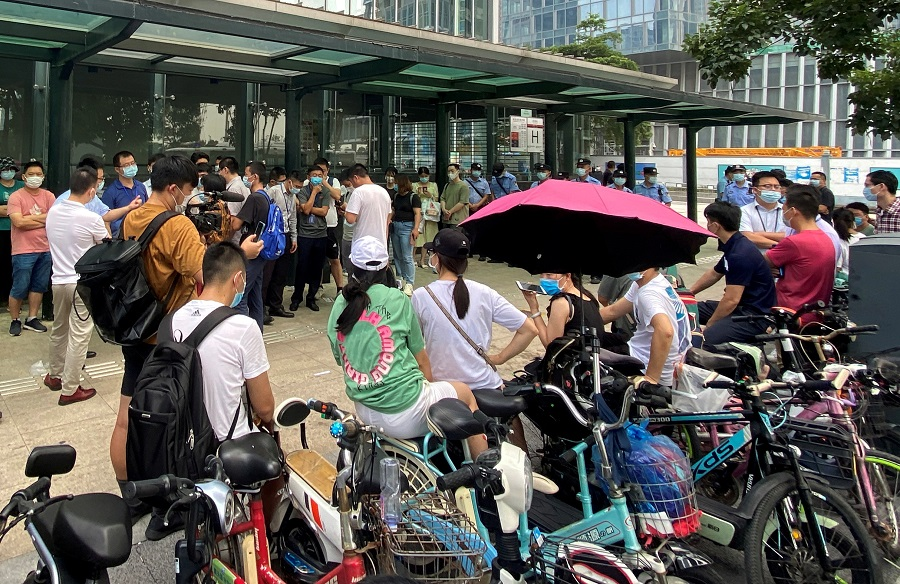 People gather to demand repayment of loans and financial products as security personnel guard outside Evergrande's headquarters in Shenzhen, China, 15 September 2021. (David Kirton/File Photo/Reuters)