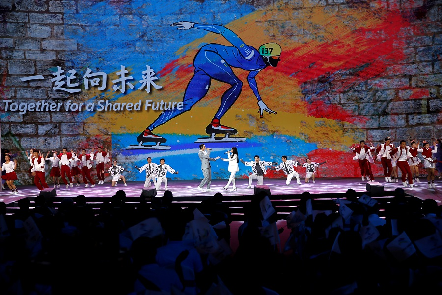 """Singers and dancers perform on stage as a giant screen shows the slogan for the Beijing 2022 Winter Games, """"Together for a Shared Future"""", at a ceremony in Beijing, China, 17 September 2021. (Tingshu Wang/Reuters)"""