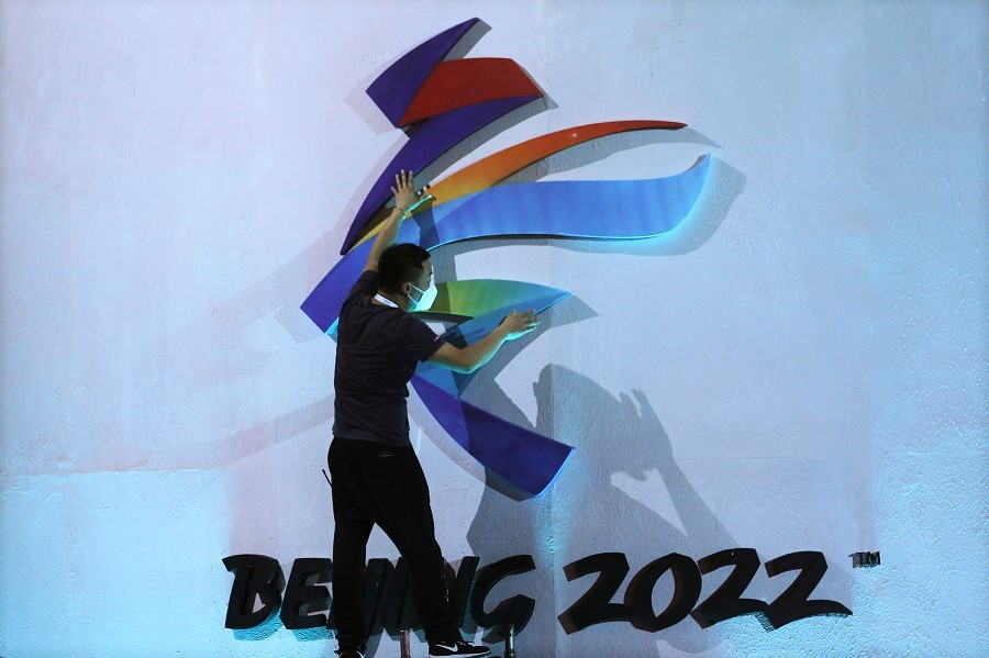 A man adjusts an emblem of the Beijing 2022 Winter Olympic Games before a ceremony unveiling the slogan, in Beijing, China, 17 September 2021. (Tingshu Wang/Reuters)