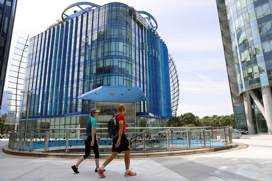 People walk past the Evergrande Center of China Evergrande Group in Shanghai, China, 24 September 2021. (Aly Song/Reuters)