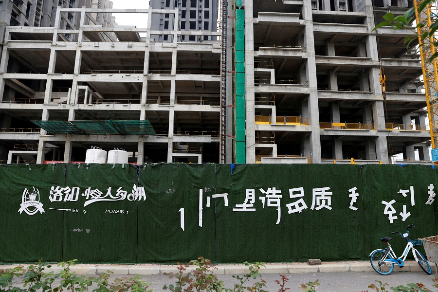A peeling logo of the Evergrande Oasis, a housing complex developed by Evergrande Group, is seen outside the construction site where the residential buildings stand unfinished, in Luoyang, China, 16 September 2021.(Carlos Garcia Rawlins/File Photo/Reuters)