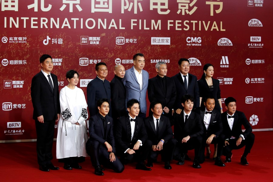 """Directors Chen Kaige, Dante Lam and Tsui Hark pose for photos with crew members of the film """"The Battle at Lake Changjin"""", during a red carpet ceremony at the Beijing International Film Festival, in Beijing, China, 30 September 2021. (Tingshu Wang/Reuters)"""
