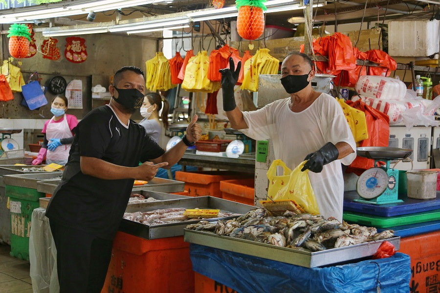 A customer poses for a photo with a stall owner at a market in Singapore. (SPH)