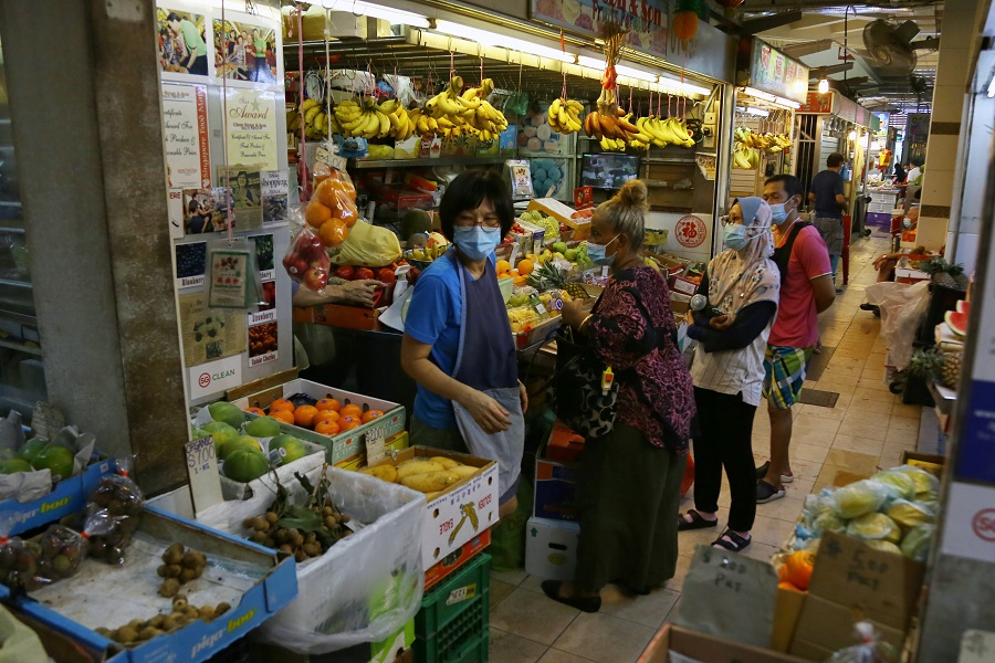 Customers buy fruits at a market in Singapore. (SPH)
