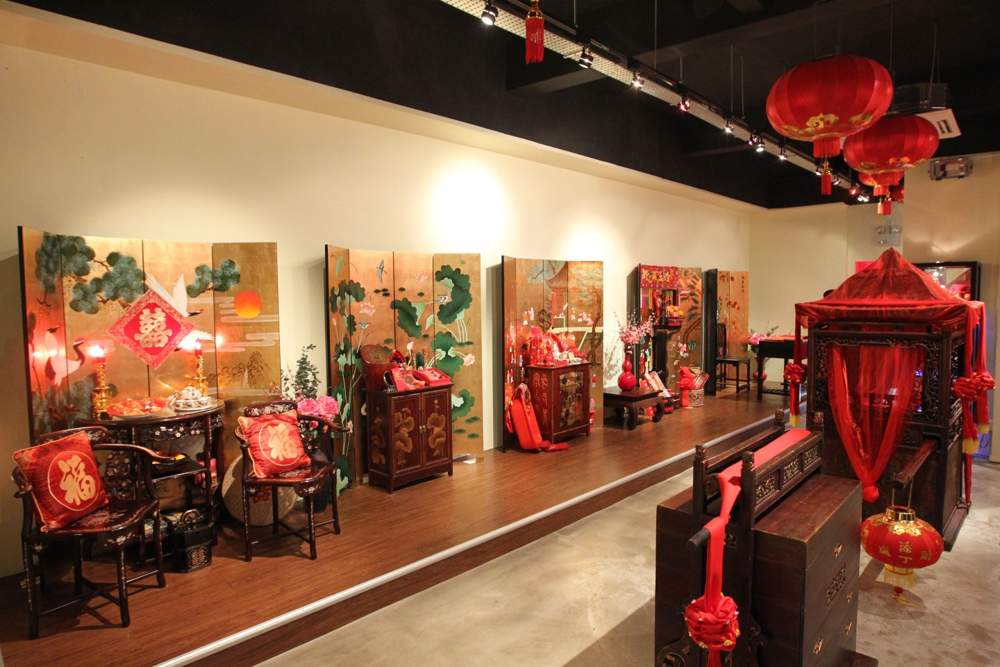 Exhibition pieces showcasing antique wedding decorations and a Chinese wedding sedan chair. (SPH)