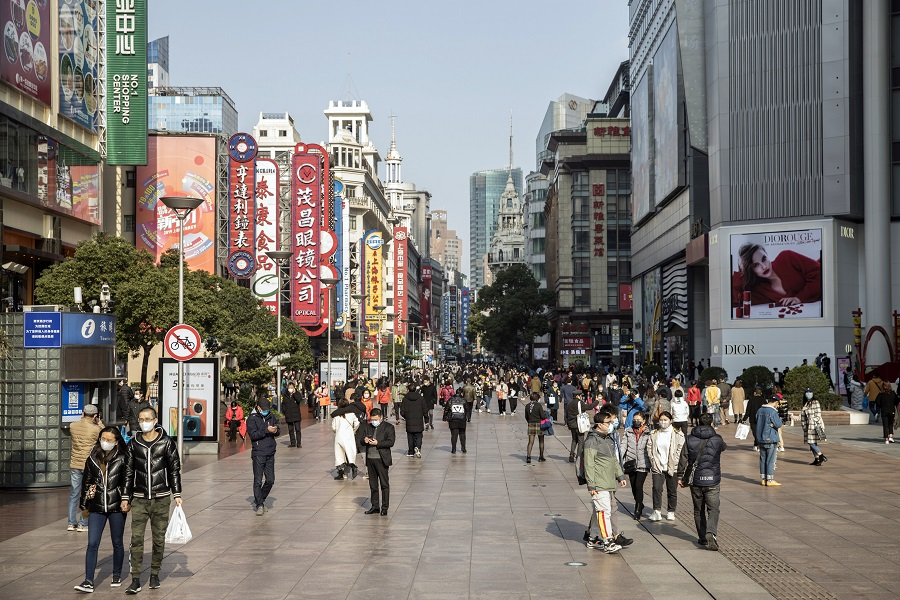 Shoppers and pedestrians wearing protective masks walk past stores on Nanjing Road in Shanghai, China, on 14 March 2020 as China returns to work slowly. (Qilai Shen/Bloomberg)