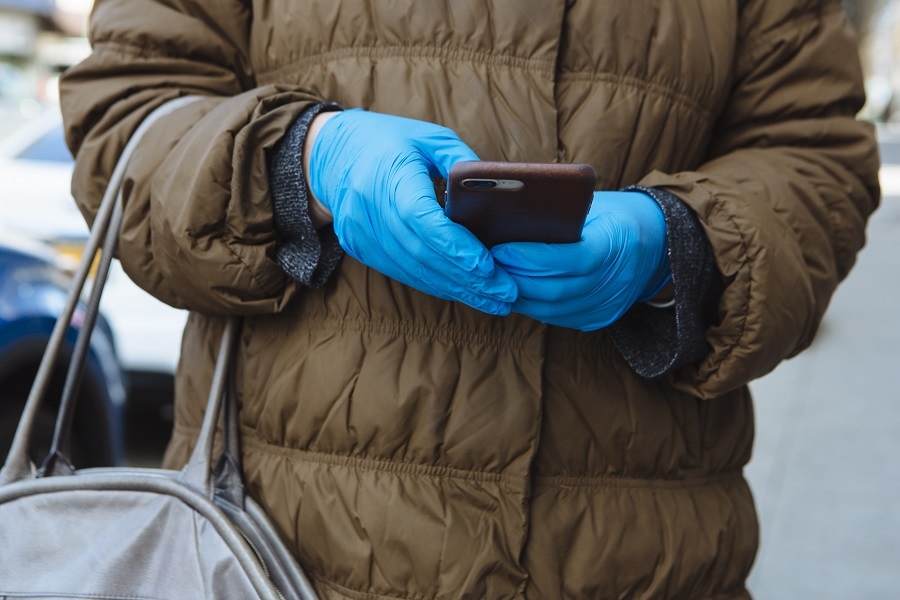 A person wears protective gloves while using a mobile phone in New Rochelle, New York, U.S., on 16 March 2020. (Angus Mordant/Bloomberg)