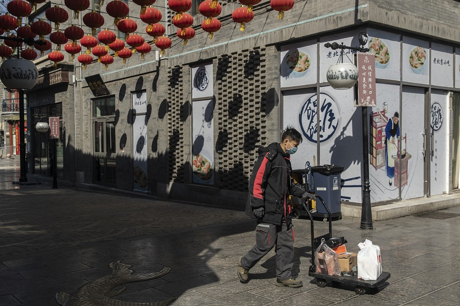 A courier pushes a cart down a quiet shopping street in the Qianmen area of Beijing, China, on 17 March 2020. (Qilai Shen/Bloomberg)