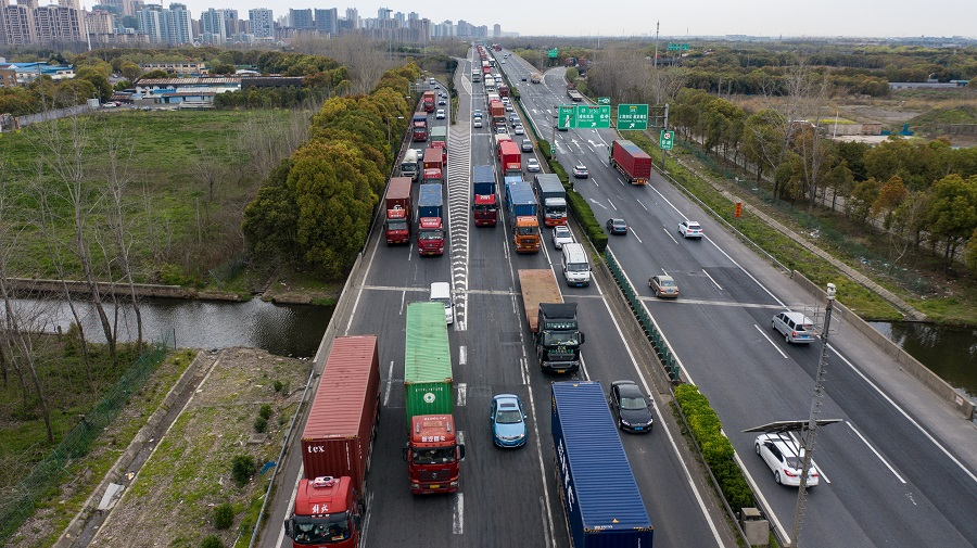 Freight trucks and other vehicles travel on a highway in this aerial photograph taken in Shanghai, China, on 25 March 2020. While much of the world's output is grinding to a halt because of the coronavirus, China is slowly emerging from its shutdowns by restarting production at factories and resuming some flights. (Qilai Shen/Bloomberg)