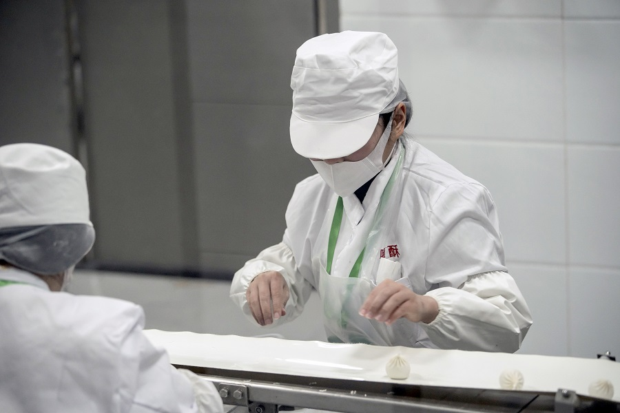 An employee wearing a protective mask works on the dumpling production line at a Hi-Su Food Co. factory in Shanghai, China, on 1 April 2020. (Qilai Shen/Bloomberg)