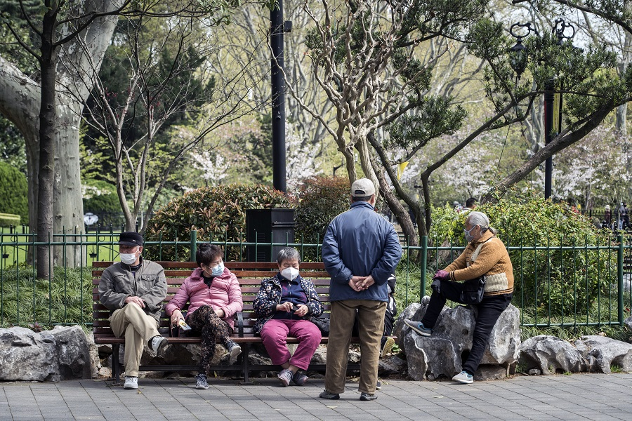 People wearing protective masks sit on a bench at Lu Xun Park in Shanghai, China, on 2 April 2020. (Qilai Shen/Bloomberg)