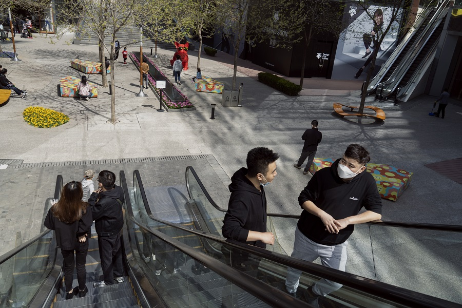 People wearing protective masks ride on an escalator in a shopping area in Beijing, China, on 4 April 2020. (Giulia Marchi/Bloomberg)