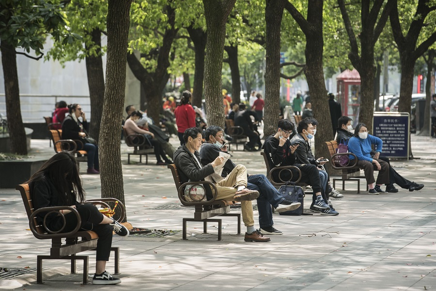 People, some wearing protective masks, sit on benches along Nanjing Road in Shanghai, China, on 20 April 2020. (Qilai Shen/Bloomberg)