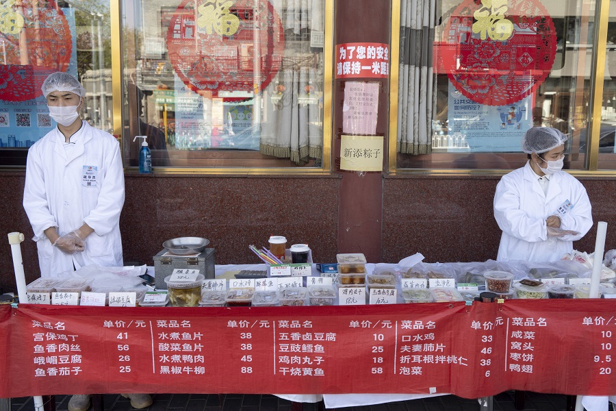 China's F&B industry is badly hit by the Covid-19 pandemic. In this photo taken on 23 April 2020, employees wearing protective masks stand behind takeaway food displayed on a table outside a restaurant in Beijing, China. (Giulia Marchi/Bloomberg)