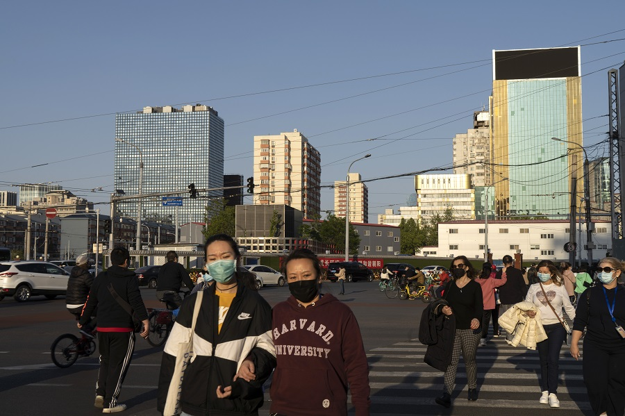 Pedestrians wearing protective masks cross a road in the Dongdaqiao area of Beijing, China, on 23 April 2020. (Giulia Marchi/Bloomberg)
