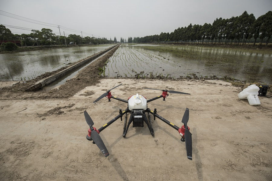 A pesticide-spraying drone waits to be loaded with batteries and payload at a newly planted rice field on Chongming Island in Shanghai, China, on 18 May 2020. (Qilai Shen/Bloomberg)