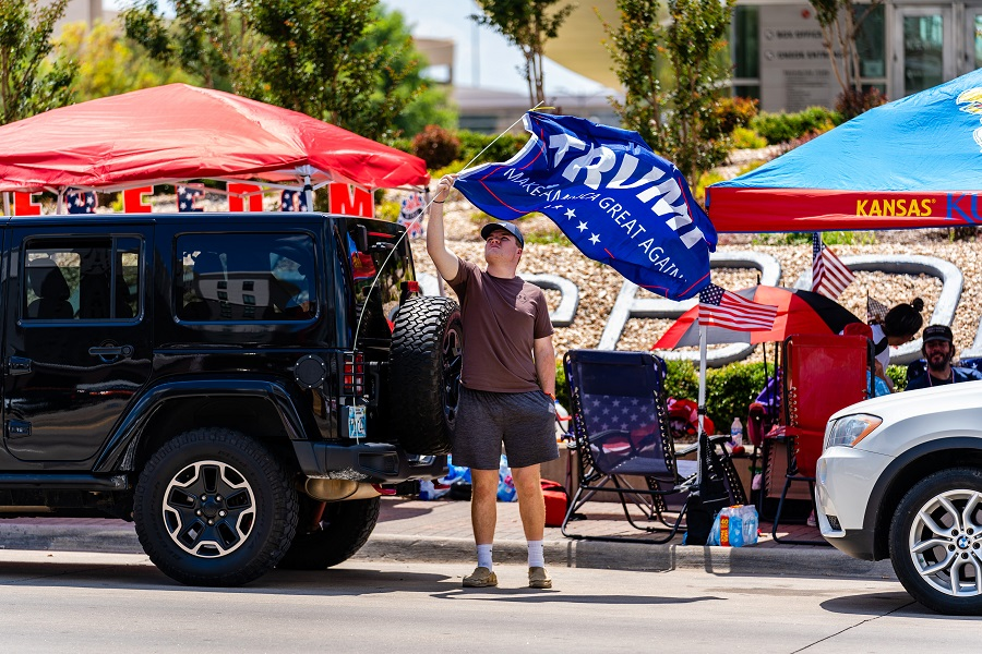 A person adjusts a campaign flag displayed on a vehicle outside of the BOK Center ahead of a rally for US President Donald Trump in Tulsa, Oklahoma, US, on 17 June 2020. (Christopher Creese/Bloomberg)