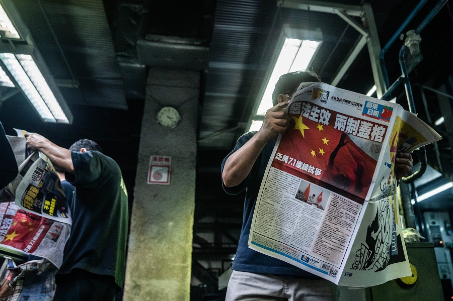 An employee proofreads a copy of the Apple Daily newspaper, published by Next Media, at the company's printing facility in Hong Kong, early on Wednesday, July 1, 2020. The headline reads: Birth of evil law, death of two systems. Photographer: Lam Yik/Bloomberg