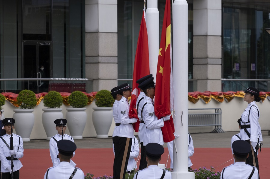 A Hong Kong Police Force Guard of Honor raises the flags of China, front, and the Hong Kong Special Administrative Region (HKSAR) during a ceremony to mark the 23rd anniversary of Hong Kong's return to Chinese rule in Hong Kong, China, 1 July 2020. (Roy Liu/Bloomberg)