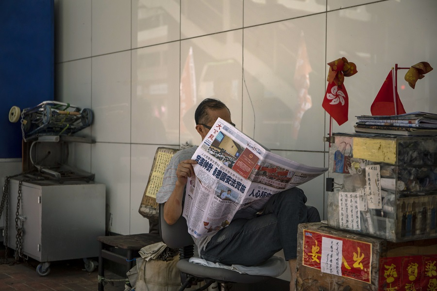 A stallholder reads a copy of the Ta Kung Pao newspaper showing a report on the passage of the new national security law in Hong Kong. The headline reads: The magic ballast -- National security law for Hong Kong implemented. Photographer: Paul Yeung/Bloomberg