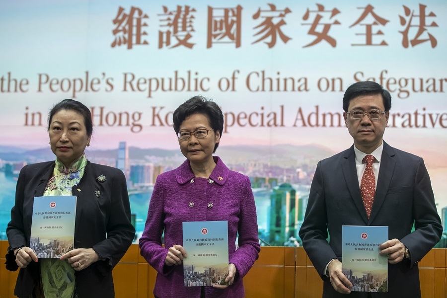 Teresa Cheng, Hong Kong's secretary for justice, from left, Carrie Lam, chief executive and John Lee, secretary for security hold copies of the new national security law at a news conference in Hong Kong, China, on 1 July 2020. (Paul Yeung/Bloomberg)