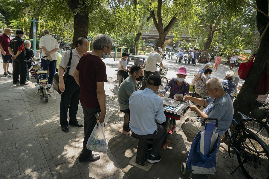 People wear protective masks while playing cards at a park in Beijing, China, on 6 July 2020. (Giulia Marchi/Bloomberg)