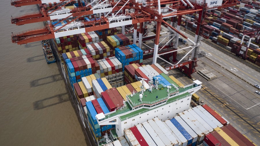 A vessel loaded with shipping containers is docked at the Yangshan Deepwater Port in this aerial photograph taken in Shanghai, China, on 12 July 2020. (Qilai Shen/Bloomberg)