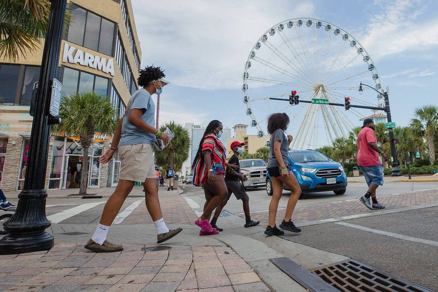 Pedestrians wearing protective mask cross a street in Myrtle Beach, South Carolina, US, on 19 August 2020. (Micah Green/Bloomberg)