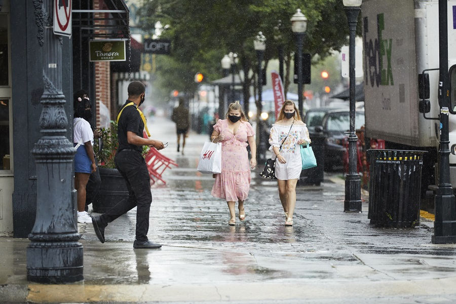 Pedestrians wearing protective masks carry shopping bags while walking along Broughton Street in the rain in Savannah, Georgia, US, on 19 August 2020. (Colin Douglas Gray/Bloomberg)