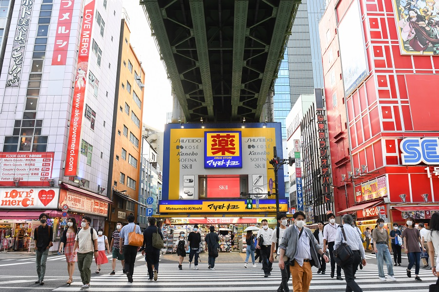 Pedestrians cross a street in front of a Matsumotokiyoshi Co. store built under railway tracks in Tokyo, Japan, on 3 September 2020. (Noriko Hayashi/Bloomberg)