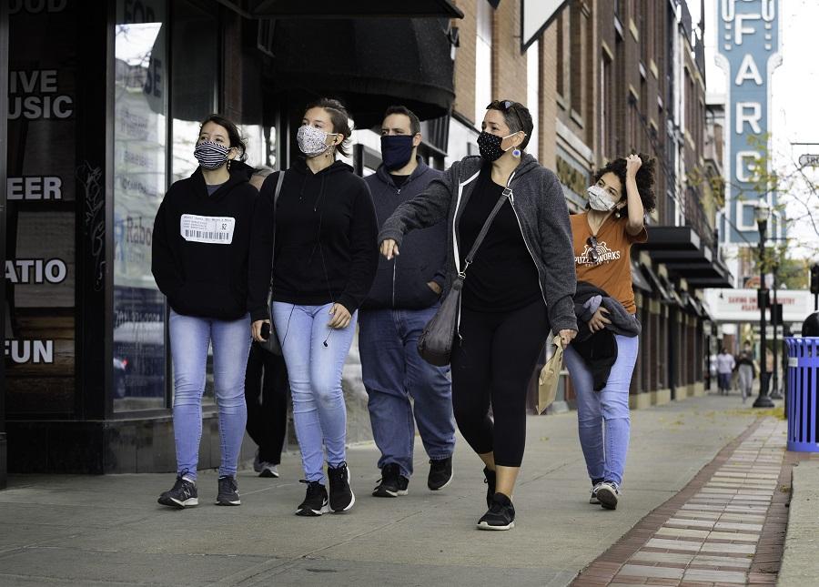 Pedestrians wearing protective masks pass in front of the Fargo Theatre in downtown Fargo, North Dakota, US, on 14 October 2020. (Dan Koeck/Bloomberg)
