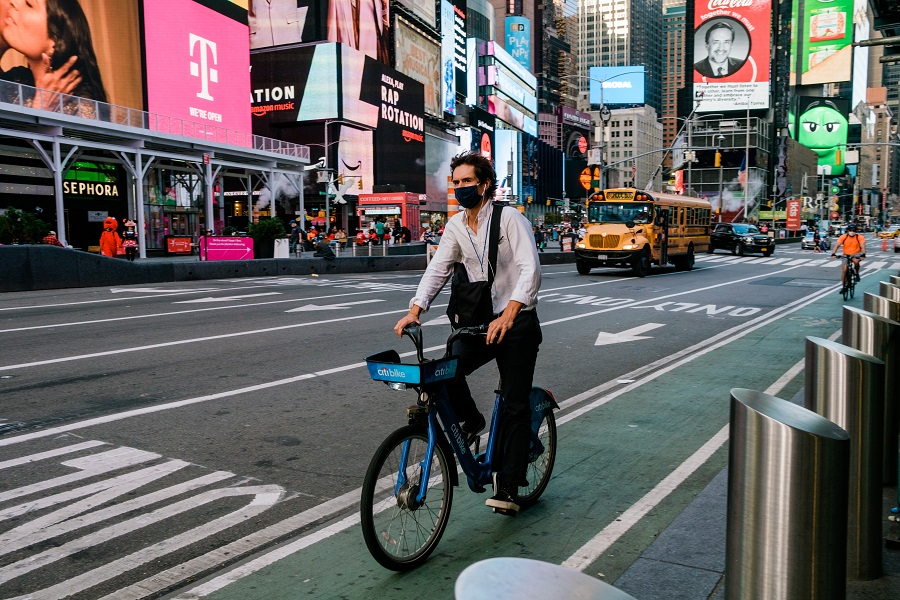 A person wears a protective mask while riding a bicycle through the Times Square neighborhood of New York, US, on 10 November 2020. (Gabriela Bhaskar/Bloomberg)