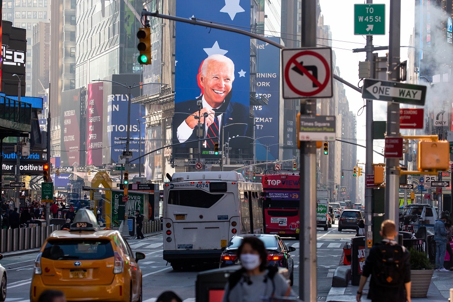 Vehicles drive past an image of US President-elect Joe Biden on a screen in the Times Square area of New York, US, on 9 November 2020. (Michael Nagle/Bloomberg)