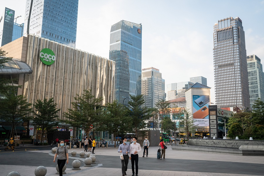 Pedestrians wearing protective masks walk past buildings in Shenzhen, China, on 20 November 2020. (Yan Cong/Bloomberg)