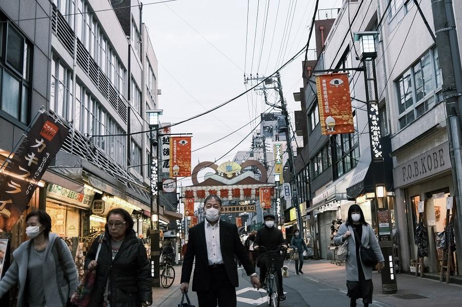 Pedestrians walk on the Sugamo Jizo-dori shopping street in the Toshima district of Tokyo, Japan, on 11 December 2020. (Soichiro Koriyama/Bloomberg)