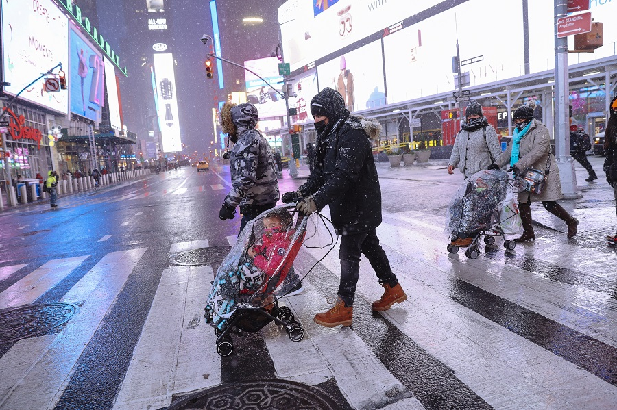 Pedestrians cross a street in the Times Square neighborhood of New York, US, 16 December 2020. (Angus Mordant/Bloomberg)