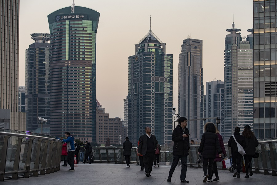 Pedestrians walk on an overpass in the Lujiazui financial district in Shanghai, China, on 21 December 2020. (Qilai Shen/Bloomberg)