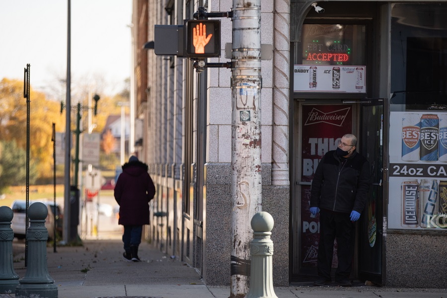 A pedestrian walks down the street as a store owner wearing a protective mask and gloves looks out the front door of a shop in downtown Pontiac, Michigan, US, on 31 October 2020. (Emily Elconin/Bloomberg)