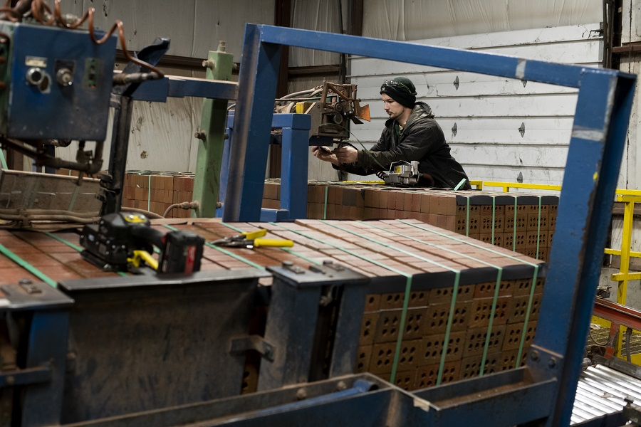 A worker wraps metal banding around pallets of fired bricks to secure them for transport at the Bowerston Shale Co. facility in Hanover, Ohio, US, on 7 January 2021. (Ty Wright/Bloomberg)