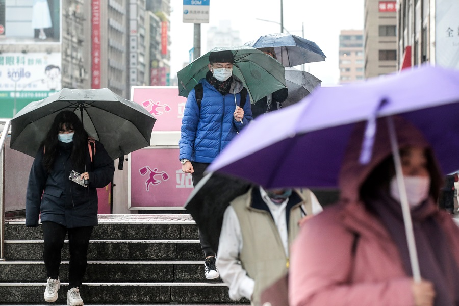 Pedestrians wearing protective masks and holding umbrellas walk along a road in Taipei, Taiwan, on 11 January 2021. (I-Hwa Cheng/Bloomberg)